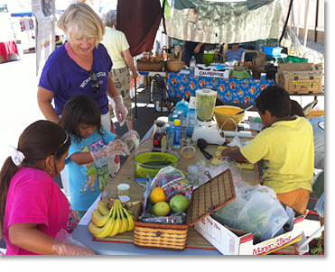 On another Sunday, WOSD member Anne Barron set up another booth and showed children how to make smoothies with fresh fruits and vegetables.