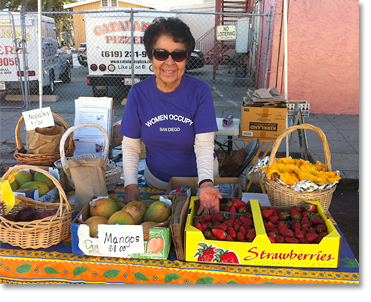 Virginia Franco showing off fresh fruits and squash blossoms (on the right) at the Women Occupy San Diego booth at Sobreruedas (30th and Imperial) n San Diego..Photos by Nic Paget-Clarke.