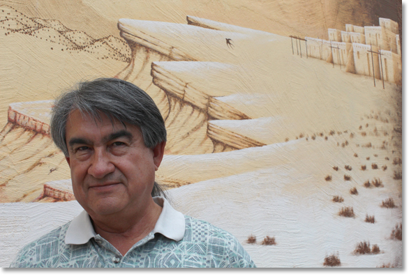 Dr. Gregory Cajete at the All Indian Pueblo Cultural Center in Albuquerque, New Mexico in front of a section of a mural by D.C. Arquero © '98. Photo by Nic Paget-Clarke.