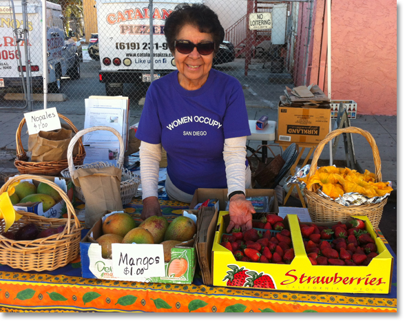 Virginia Franco showing off fresh fruits and squash blossoms (on the right) at the Women Occupy San Diego (WOSD) booth at Sobreruedas (30th and Imperial) in San Diego. Photo by Nic Paget-Clarke.'